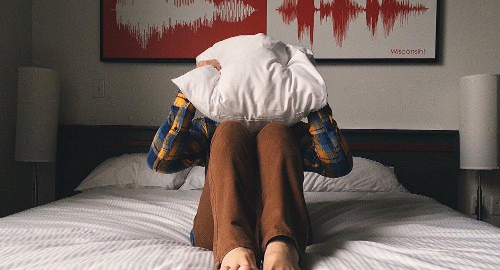 Мужчина закрывает голову подушкой