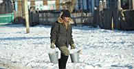 Мужчина несет воду в ведрах по улице села, архивное фото