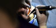 Стамотолог пациенттің тісін емдеп жатыр