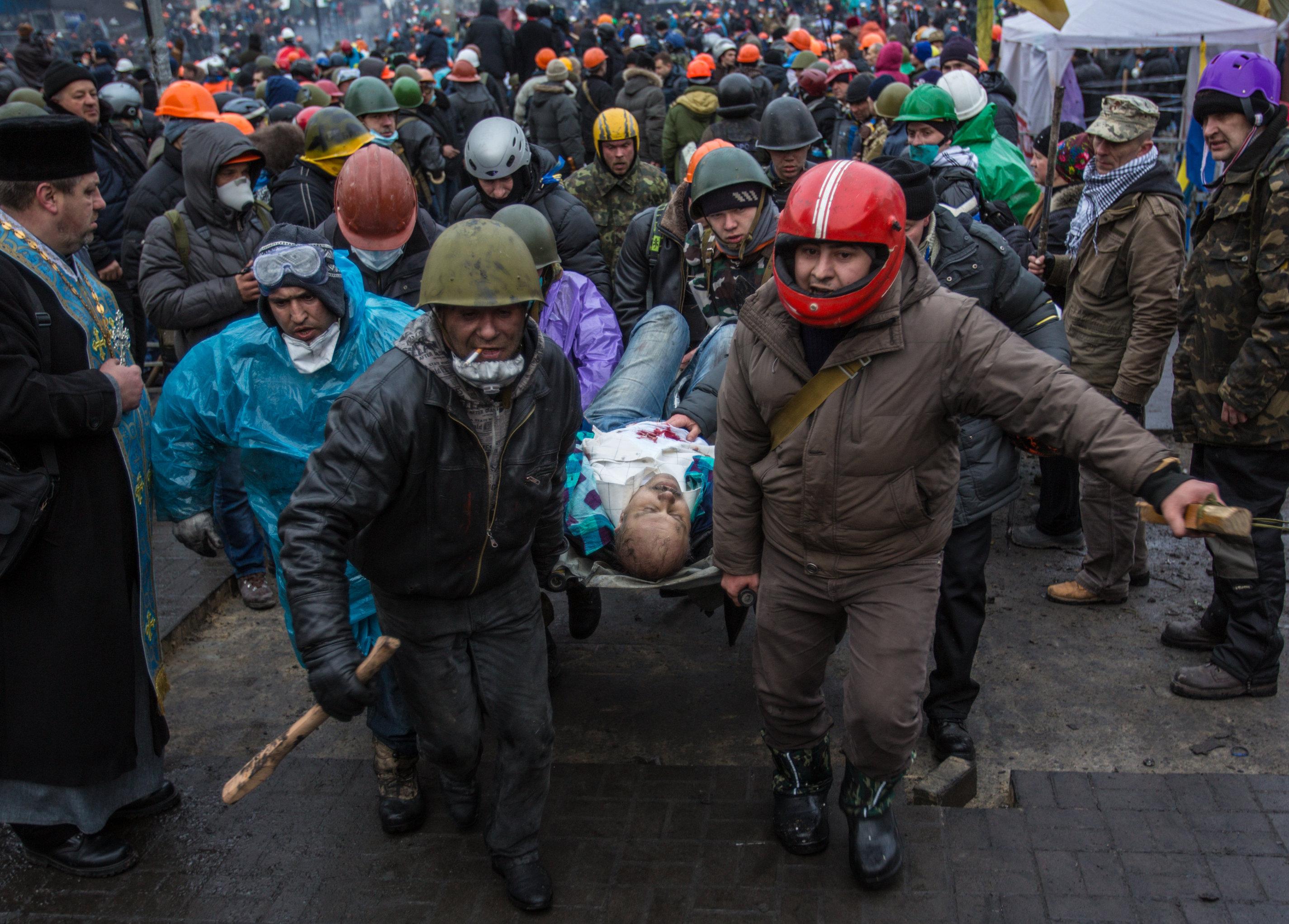 Сторонники оппозиции несут раненного во время столкновений с сотрудниками правопорядка в Киеве, архивное фото