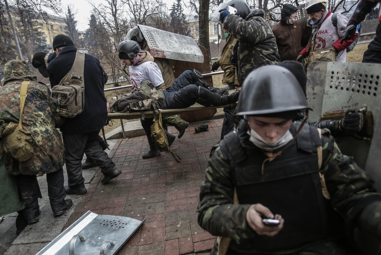 Сторонники оппозиции несут раненного во время столкновений с сотрудниками правопорядка на улице Институтской в Киеве, архивное фото