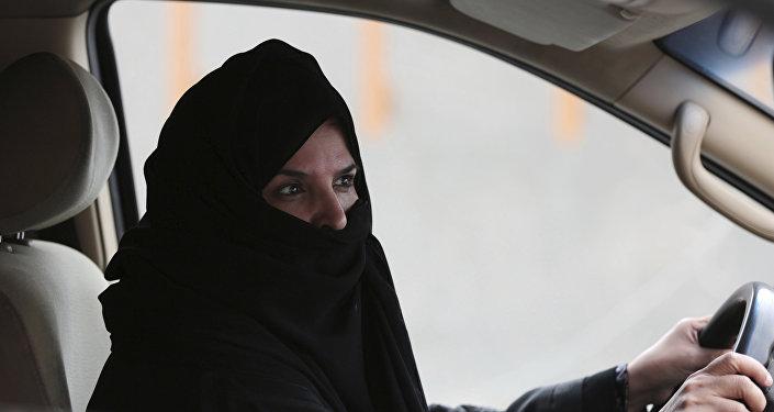 Женщина в абайе водит машину