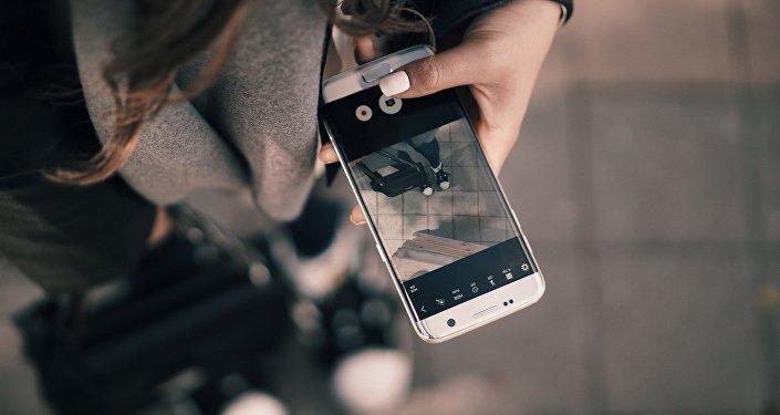 Жасөспірімнің қолындағы телефон, иллюстративті фото
