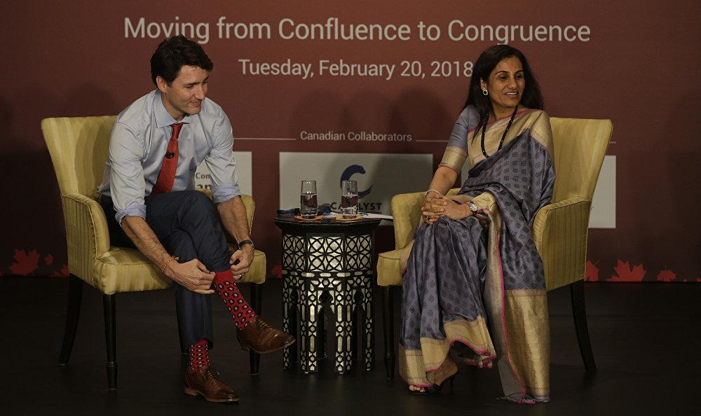 Премьер-министр Канады Джастин Трюдо поправляет свои носки во время встречи с гендиректором банка ICICI Чандой Кочхар в Мумбаи