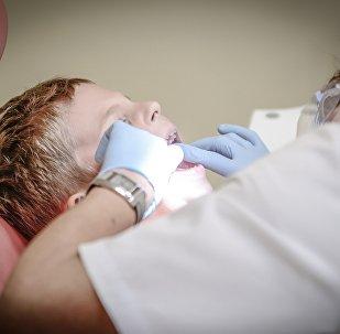 Стоматолог баланың тісін емдеп жатыр, архивтегі фото