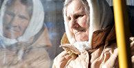 Пожилая женщина смотрит в окно автобуса, архивное фото