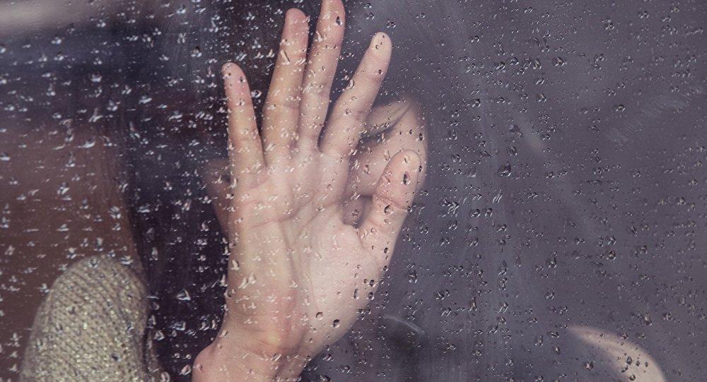 Девушка смотрит в окно, иллюстративное фото