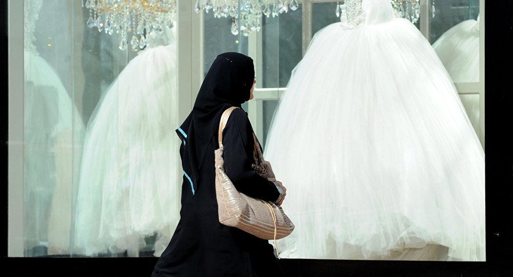 Женщина в мусульманской одежде проходит мимо витрин со свадебными платьями, архивное фото