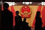 Люди на фоне герба КНР