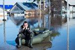 Мужчина рядом с жилыми домами, затопленными в результате паводка, архивное фото