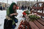 Женщина зажигает свечу в память о погибших в Кемерово