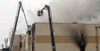 Сотрудники пожарной охраны МЧС борются с пожаром в торговом центре «Зимняя вишня» в Кемерово