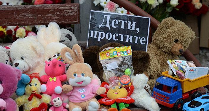 Цветы и мягкие игрушки возле здания торгового центра «Зимняя вишня» в Кемерово