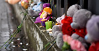 Цветы и игрушки у здания генконсульства России в Алматы в память о погибших в Кемерово