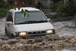 Автомобиль едет по улице во время паводка, архивное фото