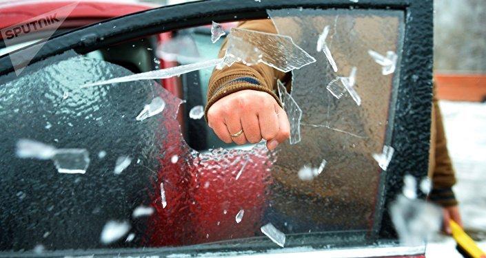 Мужчина разбивает кулаком наледь с окна своего автомобиля, архивное фото