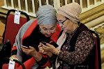 Женщины смотрят в смартфоны