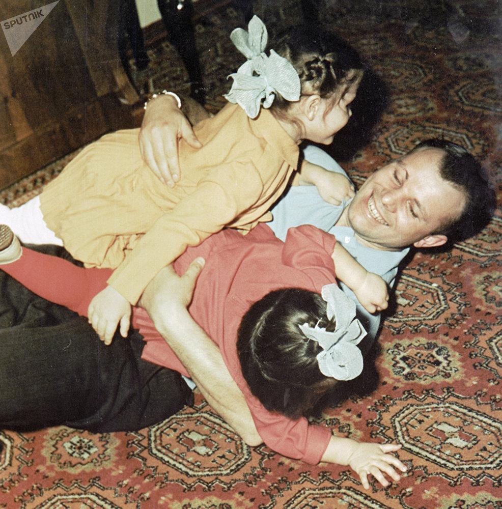Космонавт Юрий Гагарин (в центре) играет со своими дочерьми