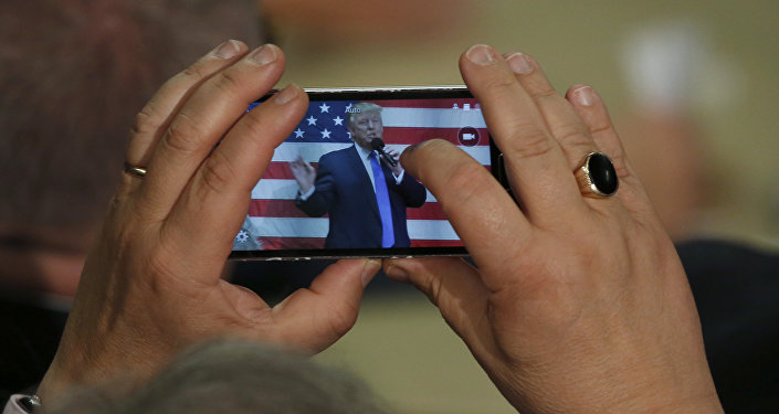 Человек фотографирует президента США Дональда Трампа