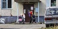 Женщина с детьми стоит у жилого дома, архивное фото