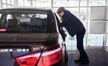 Покупатель осматривает Lifan Solano в автосалоне, архивное фото