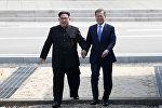 Лидер КНДР Ким Чен Ын и президент Южной Кореи Мун Чжэ Ин за руки пересекают границу в буферной зоне в Пханмунджоме