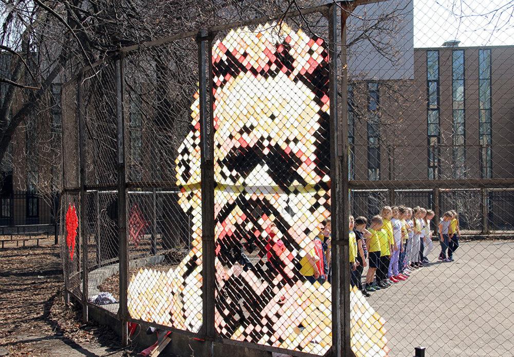 Портрет Максима Горького, выполненный из полосок клейкой ленты на скучной сетке забора спортивной площадки.
