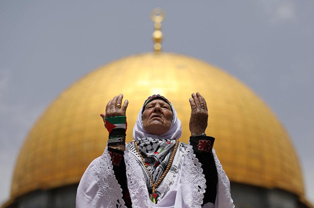 Палестинка молится на фоне мечети Купол Скалы