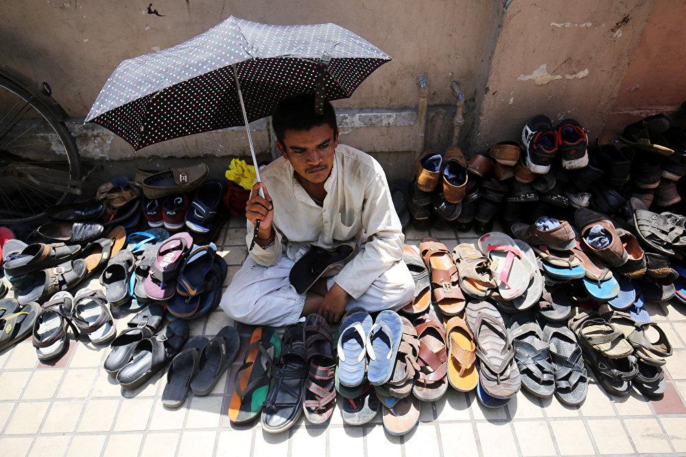 Мужчина охраняет обувь возле мечети в Индии
