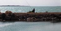 Мужчина ловит рыбу на озере Балхаш, архивное фото