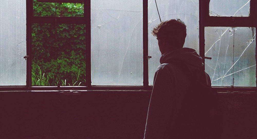 Подросток у разбитого окна, иллюстративное фото