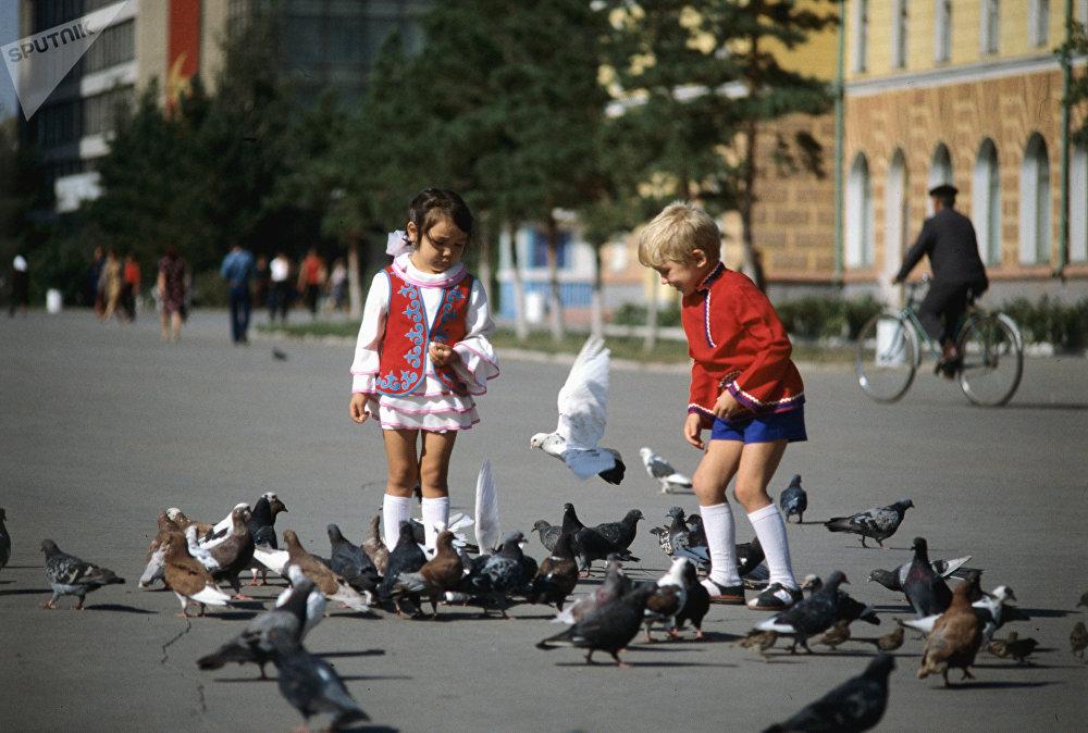 Дети кормят голубей