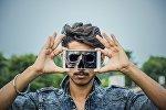 Мужчина держит сотовый телефон с изображением черепа на экране, иллюстративное фото