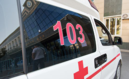 Автомобиль скорой помощи дежурит у здания, где проходит ЕНТ в Астане