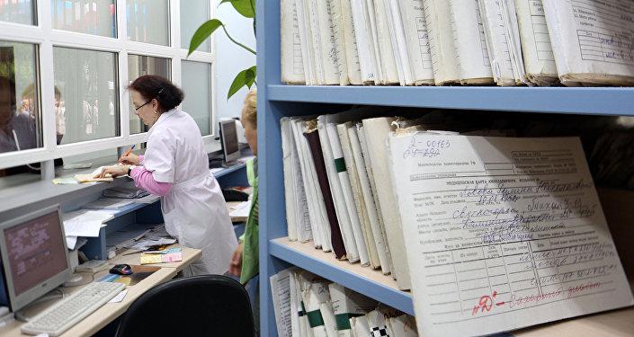Медицинский работник выдает медицинскую карту пациенту в регистратуре, архивное фото