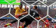 Миши Батшуайи (Бельгия) забивает гол в ворота Фарук Бен-Мустафы (Тунис)