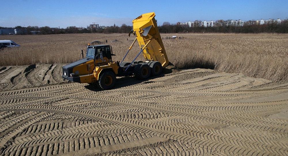 Строительная техника производит отсыпку грунта на месте предстоящего строительства, архивное фото