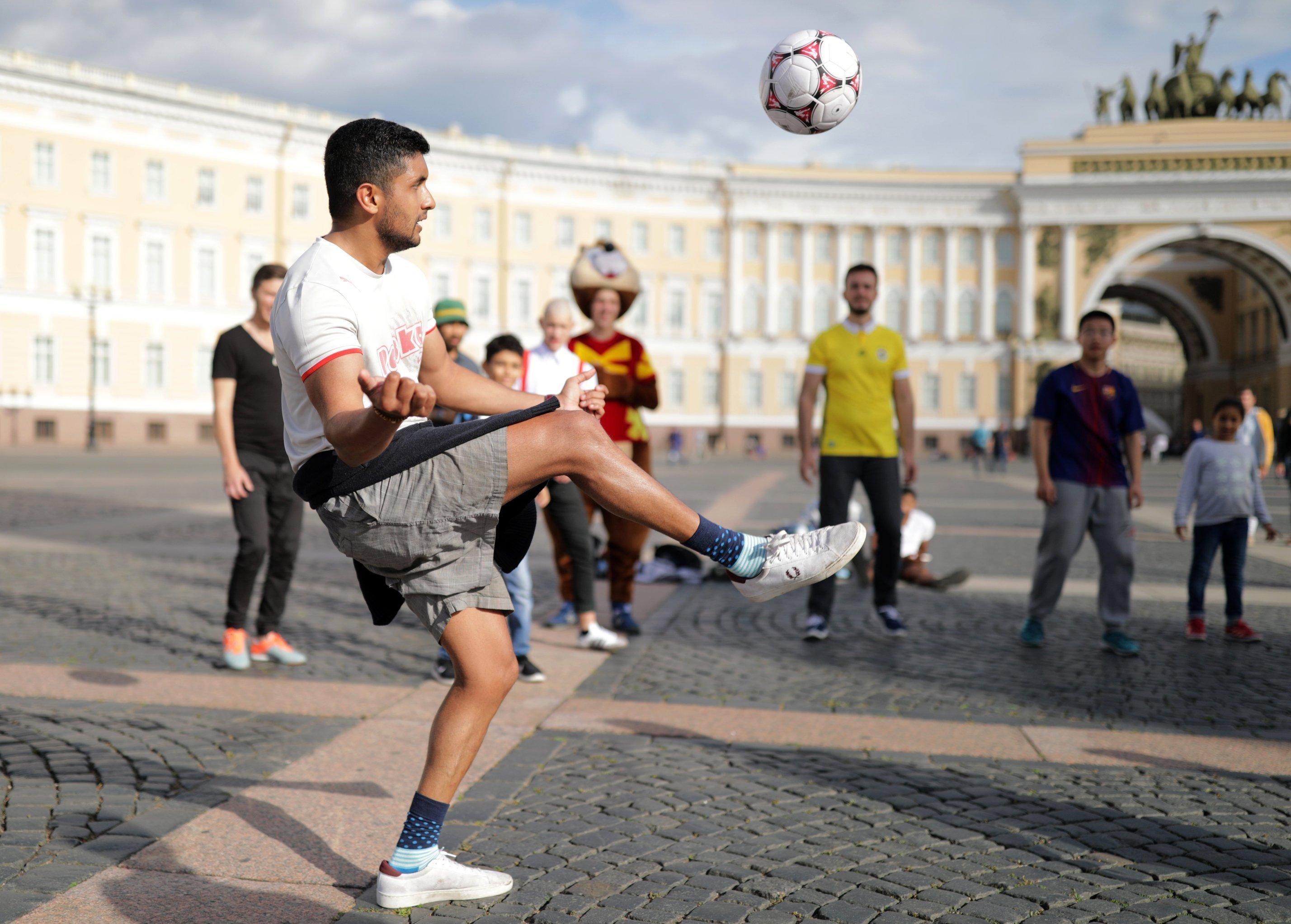 Туристы играют в мяч на Дворцовой площади в Санкт-Петербурге