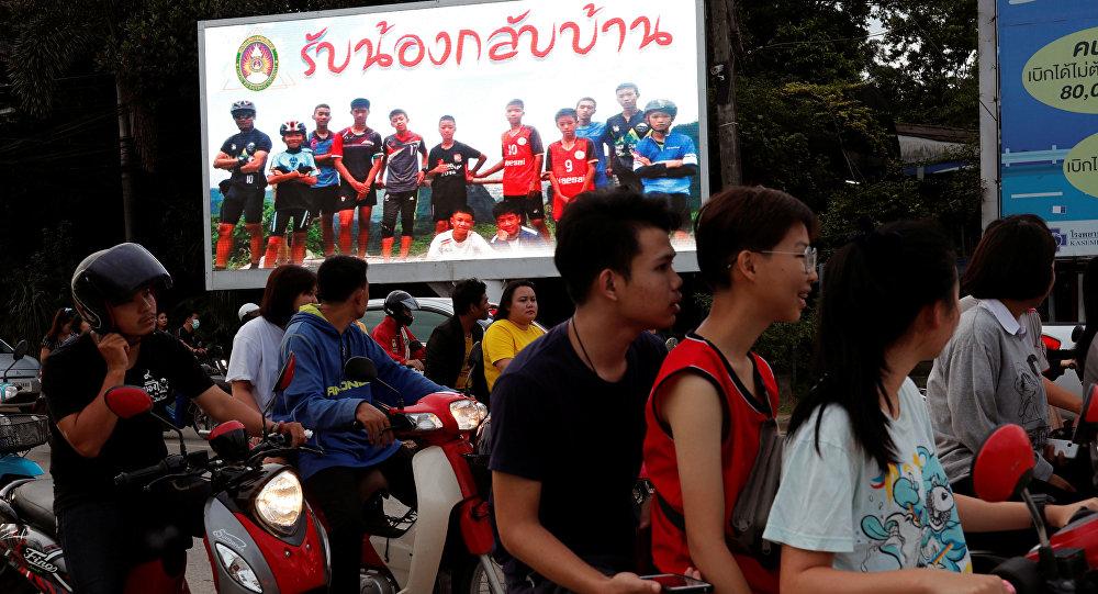 Баннер с фотографиями юных футболистов, застрявших в затопленной пещере