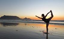Девушка на пляже занимается йогой, архивное фото