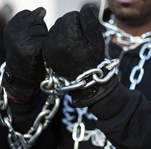 Мужчина с цепью на руках, архивное фото