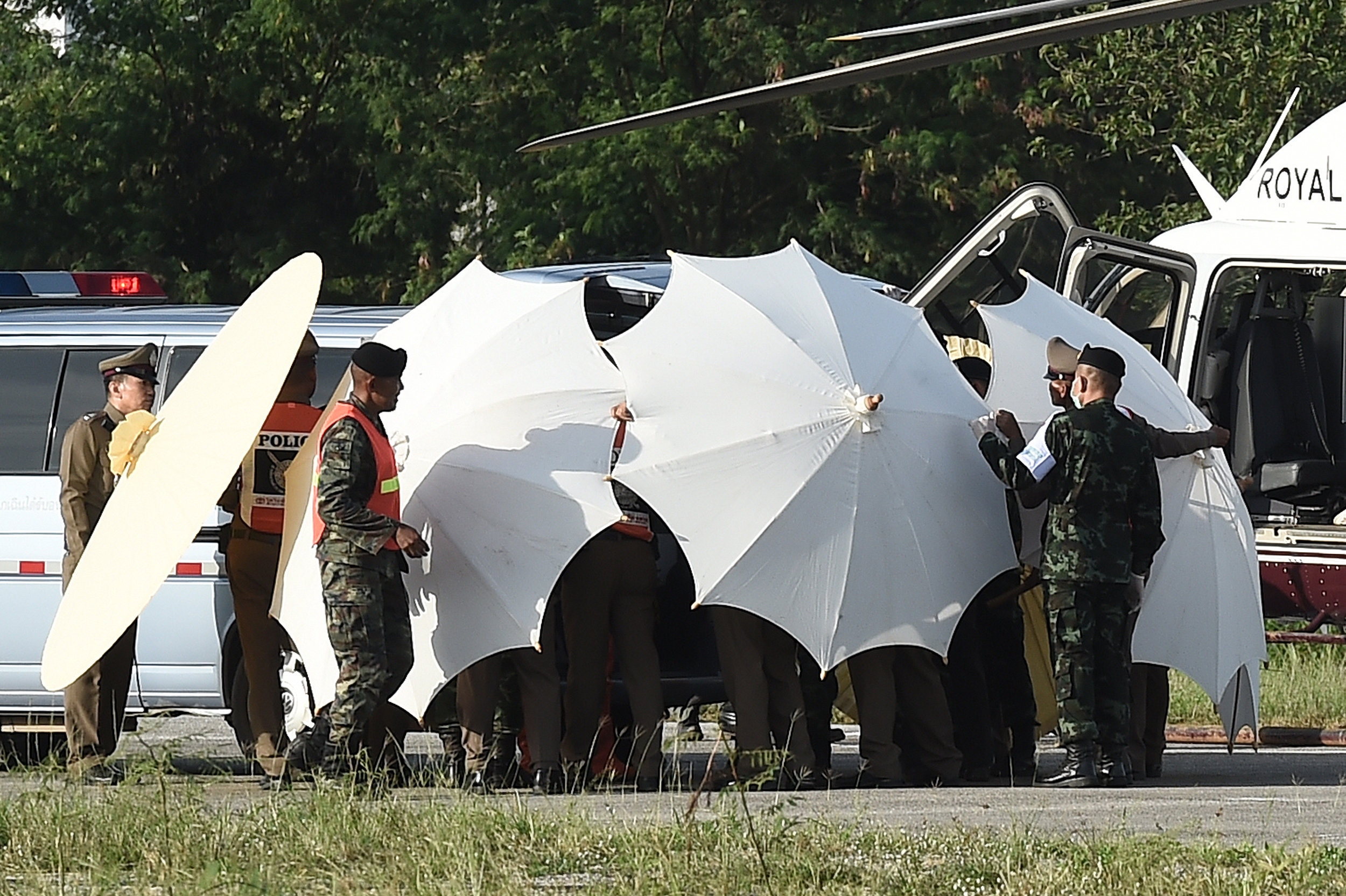 Полиция и военные с помощью непроницаемых зонтов скрывают от прессы процесс транспортировки детей