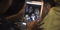 Мать одного из 12 спасенных мальчиков, демонстрирует фото, где изображены ее сын и его футбольный тренер Эккаполь Чантавун