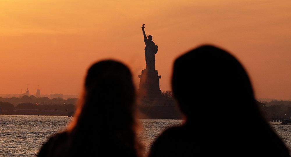 Молодые люди смотрят на Статую Свободы в Нью-Йорке на фоне заходящего солнца