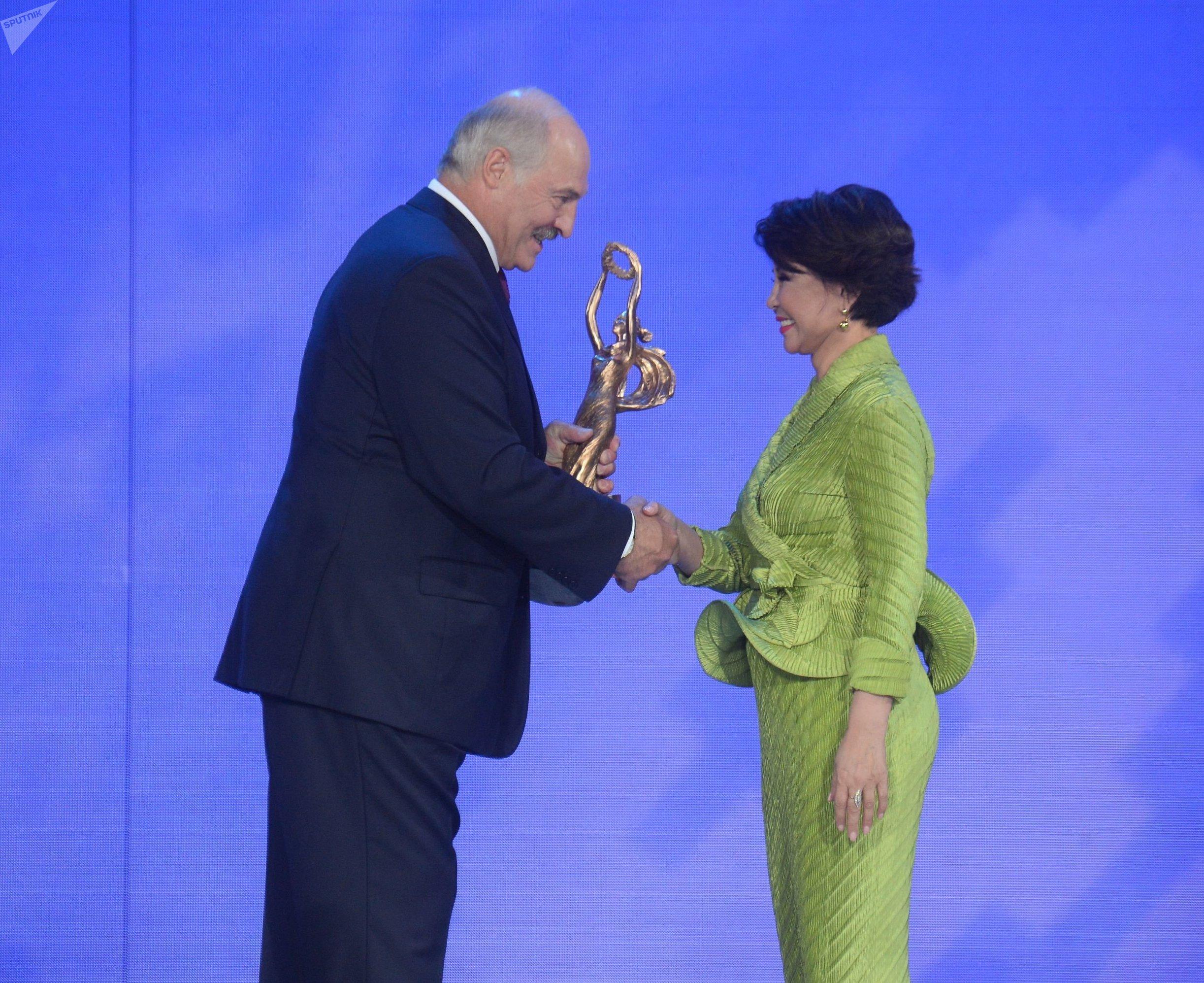 Александр Лукашенко вручает подарок Розе Рымбаевой