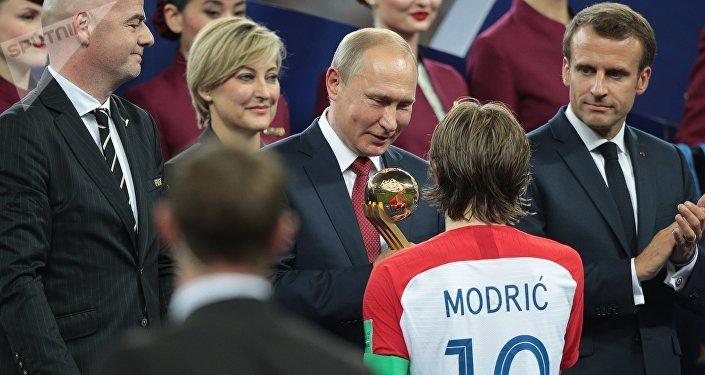 Президент ФИФА Джанни Инфантино, президент РФ Владимир Путин, Лука Модрич (Хорватия), признанный лучшим игроком чемпионата, и президент Франции Эммануэль Макрон (слева направо) на церемонии награждения победителей чемпионата мира по футболу 2018.