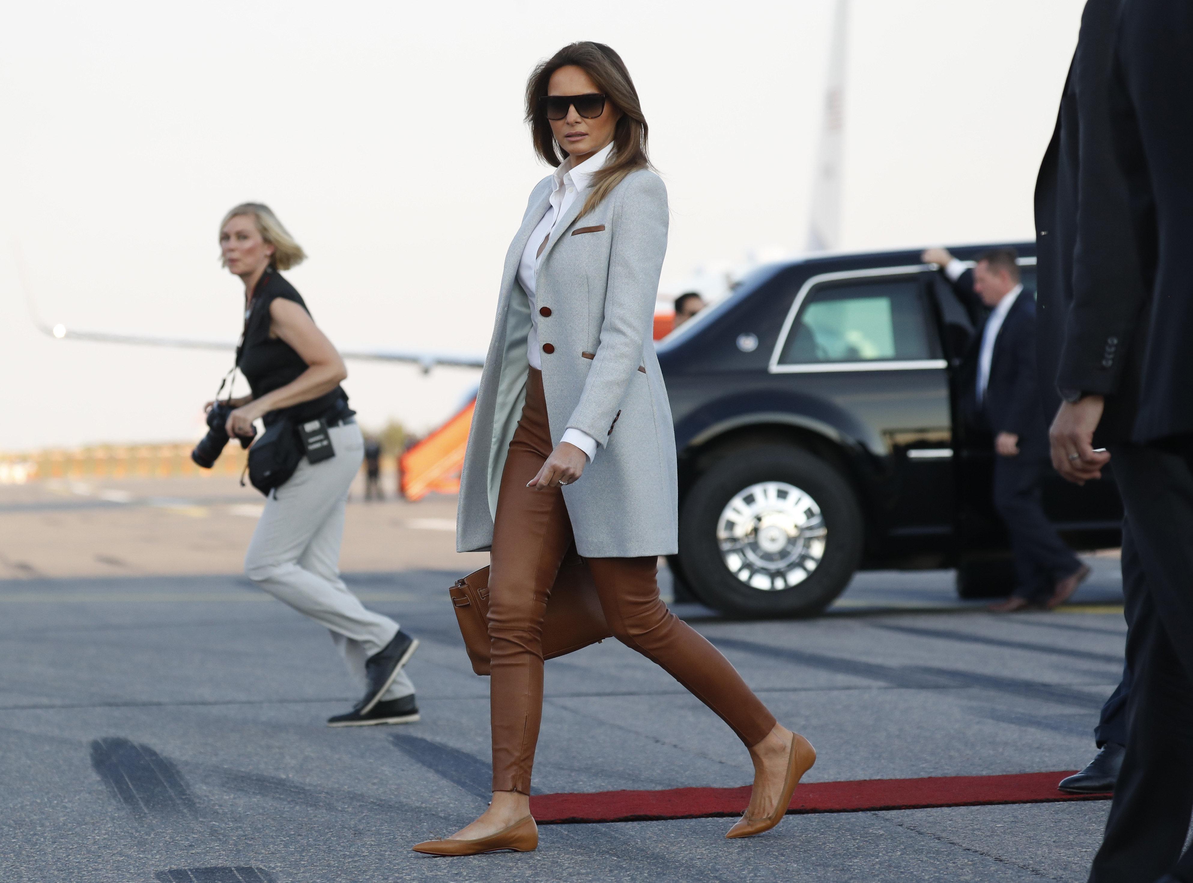 Меланья Трамп  идет к автомобилю после прибытия в Финляндию в аэропорту в Хельсинки