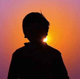 Мальчик стоит на фоне заката, иллюстративное фото