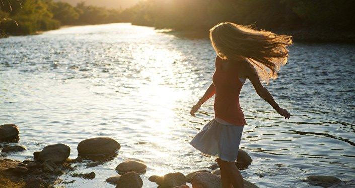 Женщина стоит на камнях у реки, иллюстративное фото