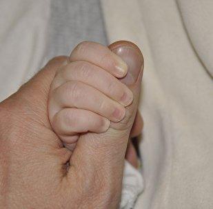 Взрослый держит за руку ребенка, иллюстративное фото